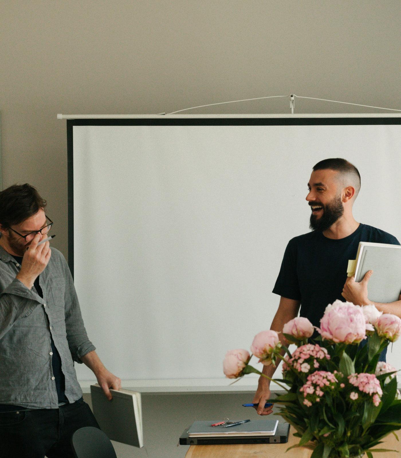 ctrl QS team members laughing standing in a meeting room